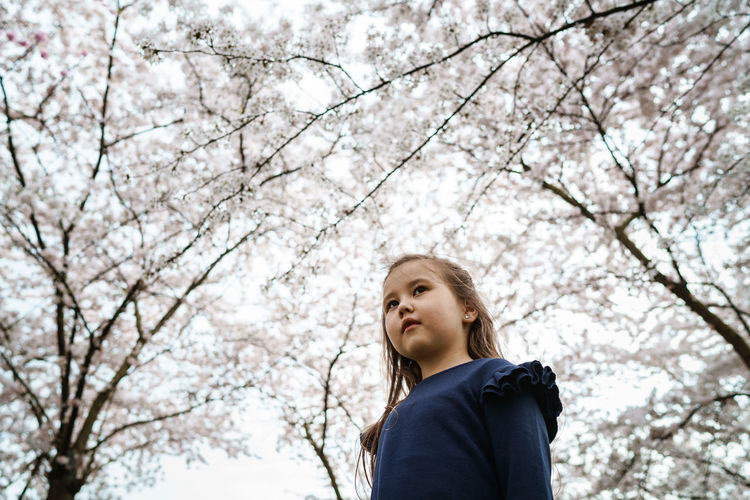 Low angle view of girl looking away against trees