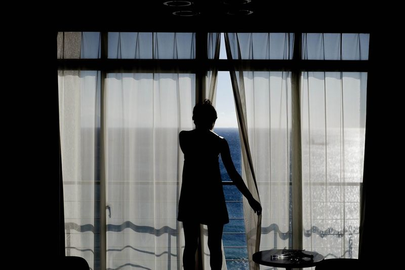 Silhouette of woman standing by window