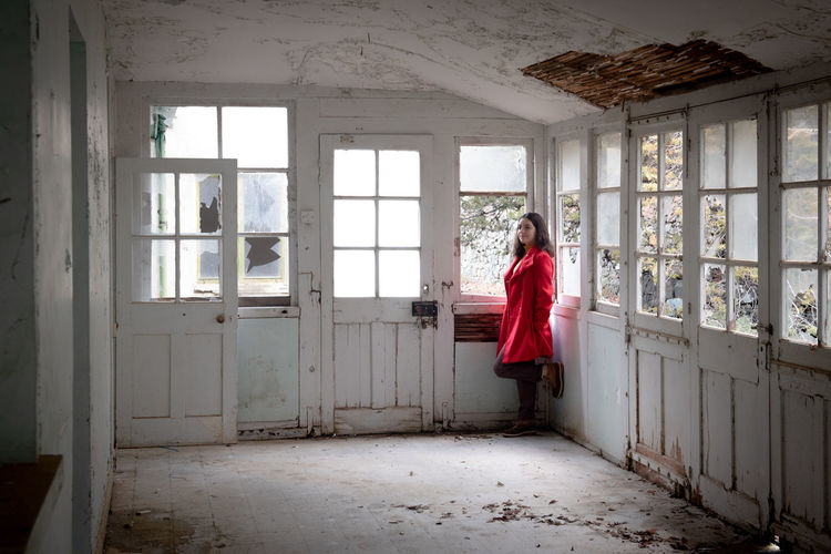 Woman standing in corridor of abandoned building