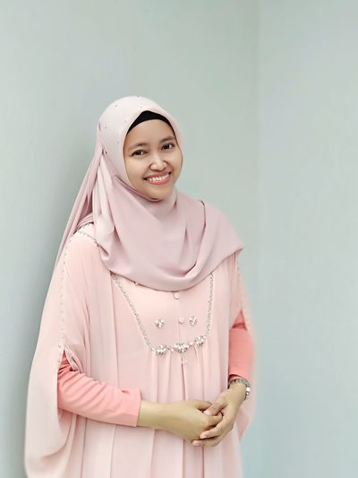 Portrait Of Young Woman Smiling While Wearing Hijab Against Wall