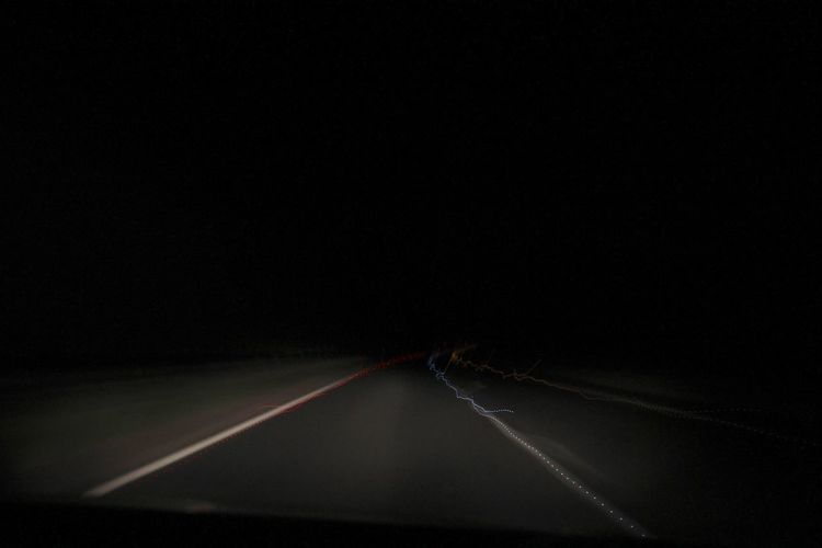 Close-up of light trails on road at night