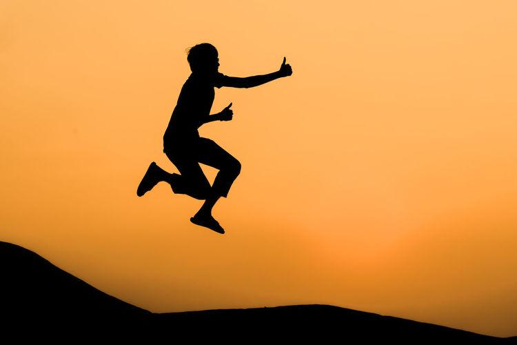 Full length of silhouette man jumping against orange sky