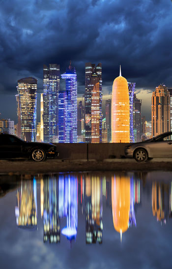 Illuminated Modern Buildings And Burj Qatar By River At Night