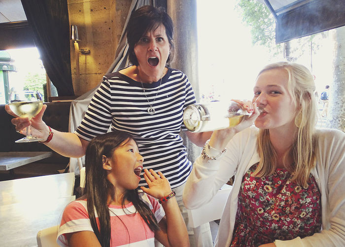 Surprised woman and girl with blond female drinking white wine at restaurant