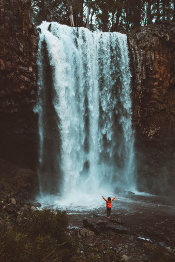 Scenic View Of Woman Standing By Waterfall