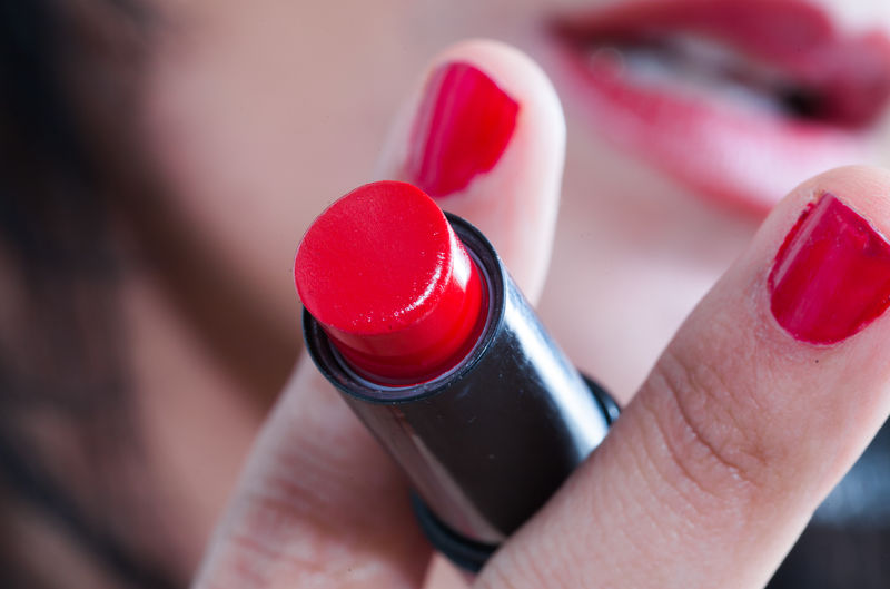 Close-up of woman hand holding red lipstick