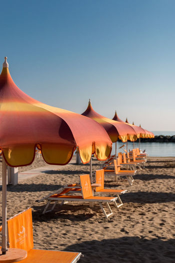 Parasols and sunbeds in Torre Pedrera near Rimini in Italy Adria Sonnenliege Strand Urlaub Baden Beach Beauty In Nature Clear Sky Copy Space Land Nature No People Orange Color Outdoors Parasol Protection Sand Scenics - Nature Sea Sky Sonnenschirme Sunlight Tranquil Scene Tranquility Water