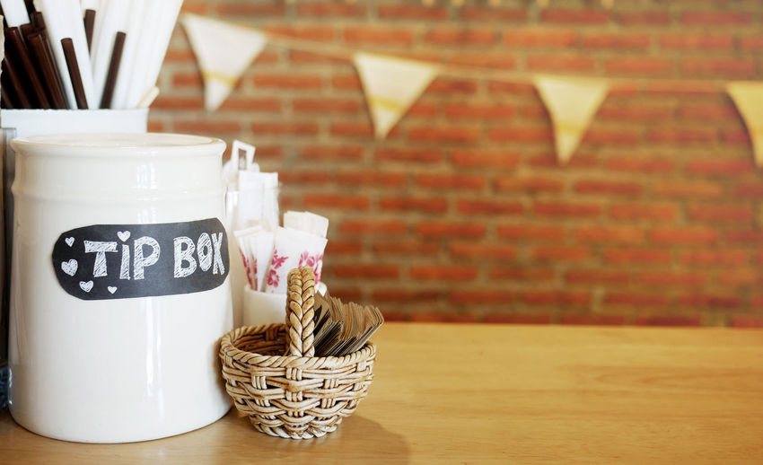 tip box decorated in coffee shop Happy People Service Art And Craft Brick Wall Capital Letter Communication Container Cup Day Exchange Focus On Foreground Food And Drink Income Indoors  Money No People Satisfaction Still Life Text Western Script