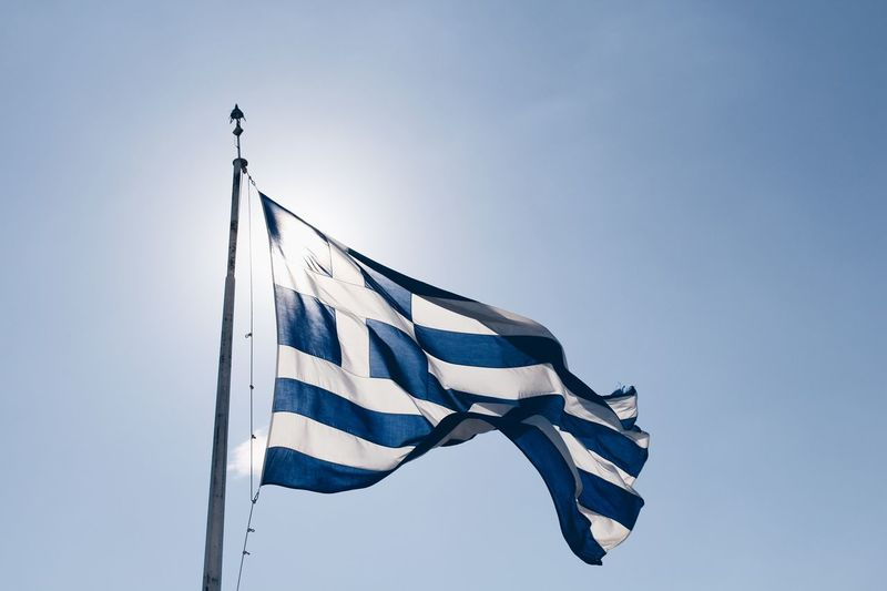 Low angle view of greek flag against clear blue sky during sunny day
