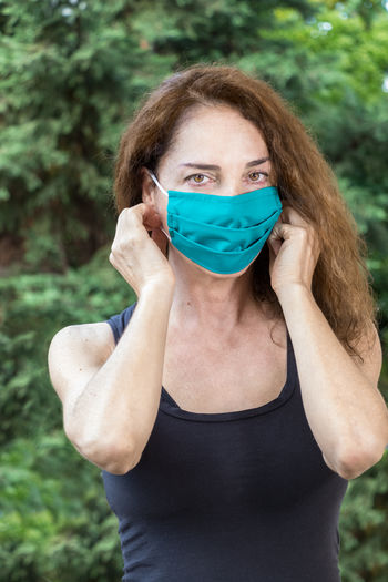 A fit woman putting on a protective mask in summer looking camera, outdoors.