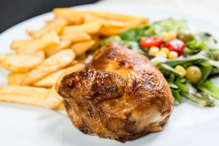 Close-up of roasted chicken with french fries and vegetables served in plate