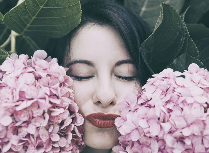 Close-up of woman with eyes closed by pink flowers
