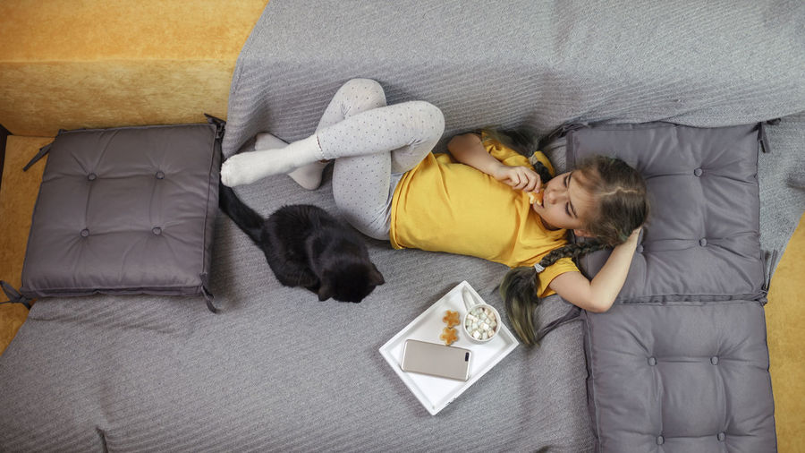 Directly above shot of girl relaxing on sofa with cat and food