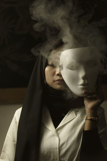 Portrait of asian woman behind the white mask