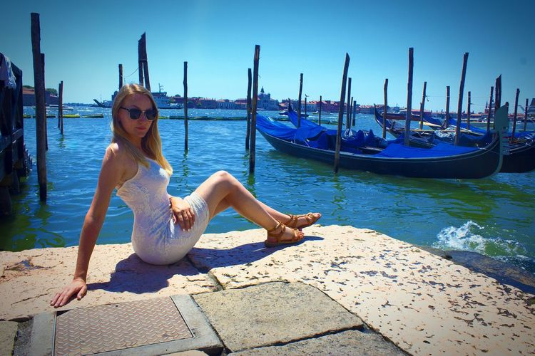 Full length of woman sitting by grand canal on sunny day