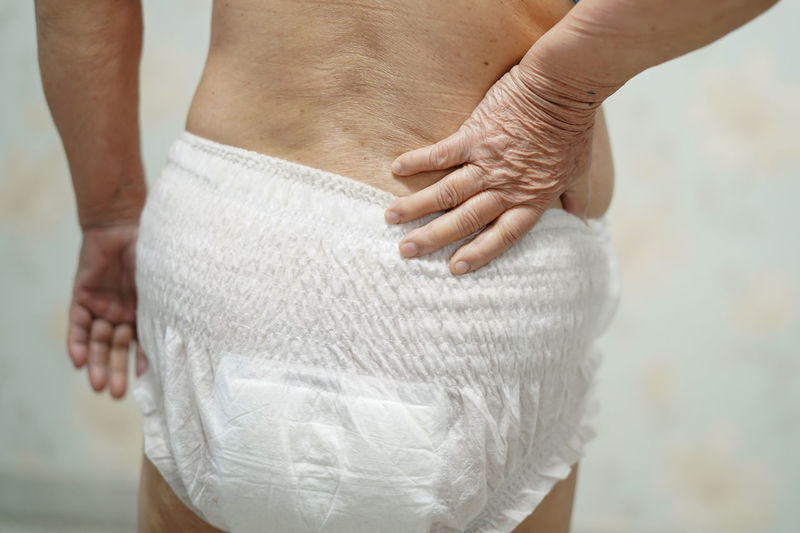 Midsection of woman touching diaper while standing against wall