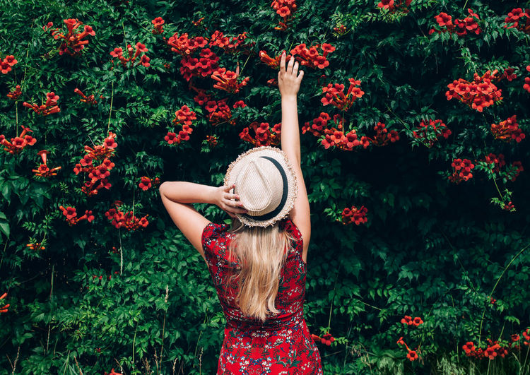 Rear view of woman standing by red flowering plant
