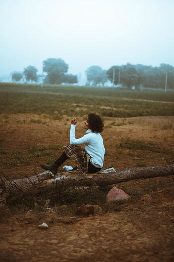 Side view of woman sitting on field
