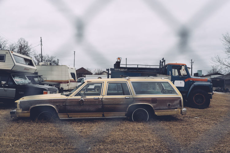 Car Chain Link Fence Day Land Vehicle Mode Of Transport No People Old Car Outdoors Shooting Through Sky Station Wagon Stationary Through The Fence Transportation Vintage Car
