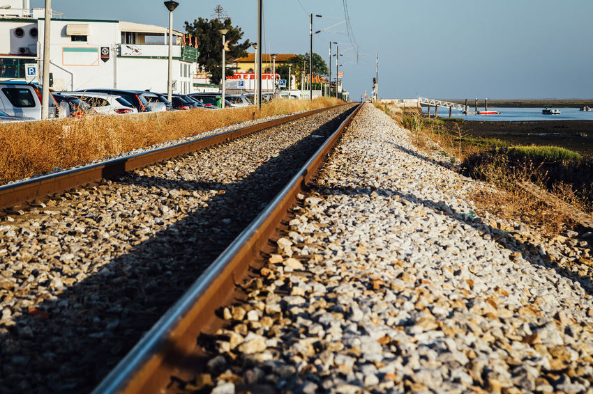 Train track of Faro, Portugal Algarve Train Tracks Architecture Day Diminishing Perspective Direction Gravel Mode Of Transportation No People Outdoors Rail Transportation Railroad Track Rock Selective Focus Sky Stone - Object Surface Level The Way Forward Track Train Transportation