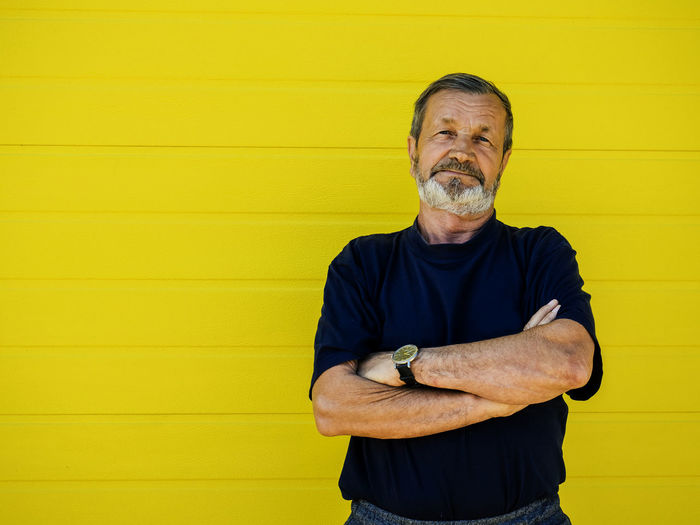 Adult Arms Crossed Beard Casual Clothing Eldery Eldery Man Facial Hair Front View Lifestyles Looking At Camera Males  Mature Men One Person Portrait Real People Senior Adult Smiling Standing Waist Up Wall - Building Feature Yellow