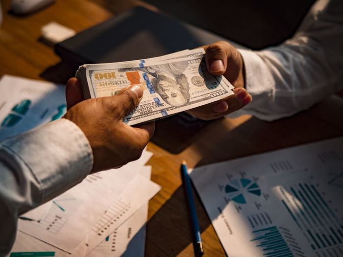 Finance Men Holding Human Hand Hand Currency Business Paper People Males  Indoors  Table Human Body Part High Angle View Paper Currency Two People Adult Document Close-up Investment