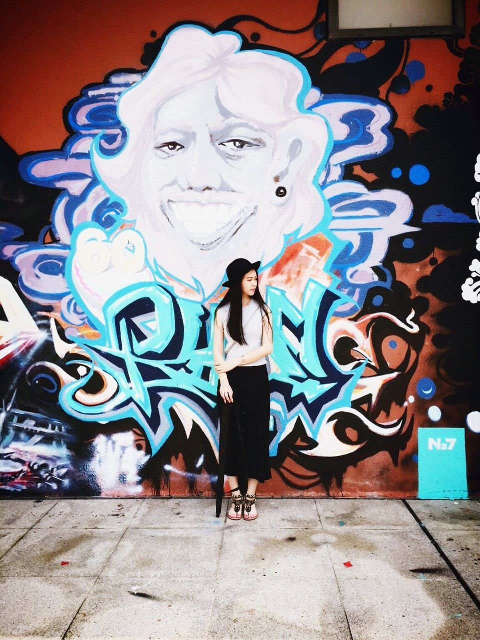 creativity, leisure activity, graffiti, art and craft, real people, lifestyles, standing, one person, full length, front view, architecture, built structure, casual clothing, multi colored, portrait, outdoors, artist, young adult, looking at camera, low angle view, young women, day, people