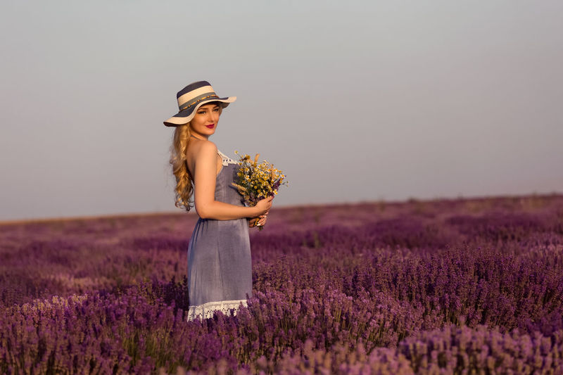 Young woman holding bouquet of wild flowers in lavender field at sunset