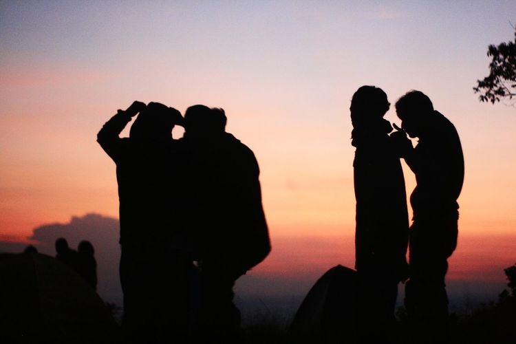 Silhouette people standing on mountain against sky during sunset