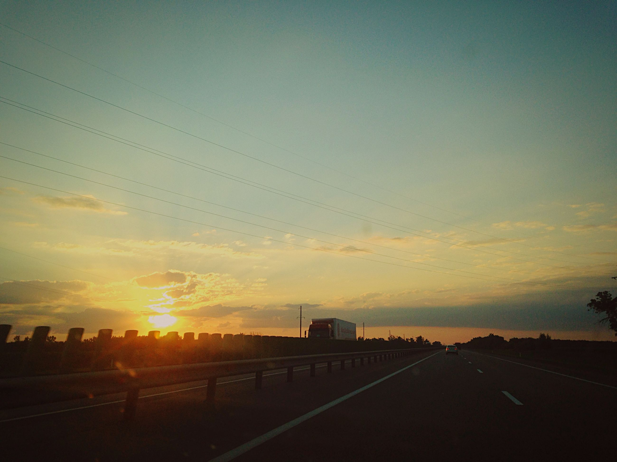 sunset, sky, silhouette, transportation, road, the way forward, orange color, cloud - sky, scenics, tranquility, sun, tranquil scene, nature, road marking, beauty in nature, diminishing perspective, landscape, sunlight, vanishing point, outdoors
