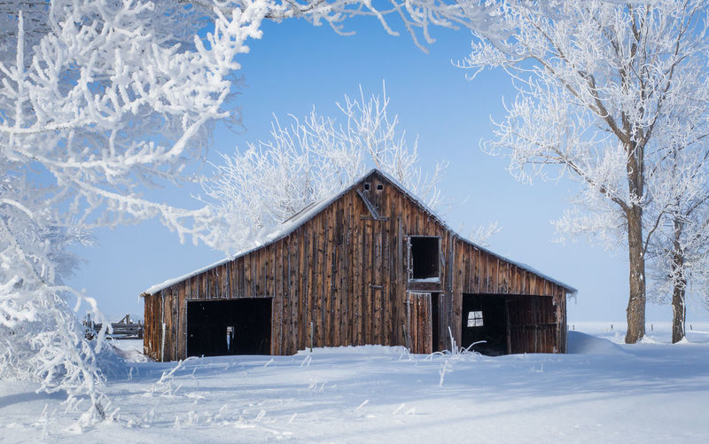 Low angle view of log cabin against sky during winter