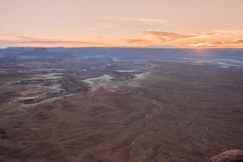 Aerial view of dramatic landscape against sky during sunset