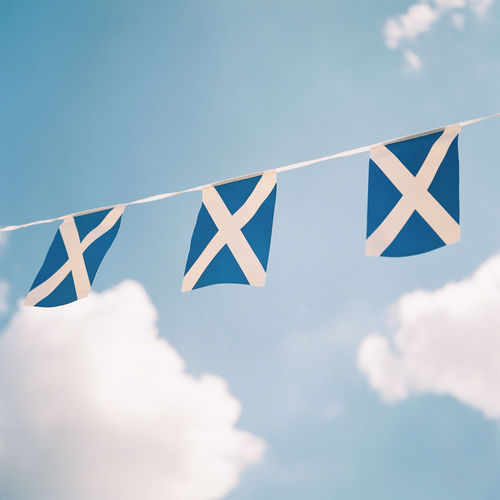 Low angle view of blue flags hanging against sky