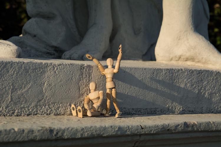 Wooden Dolls Against Statue