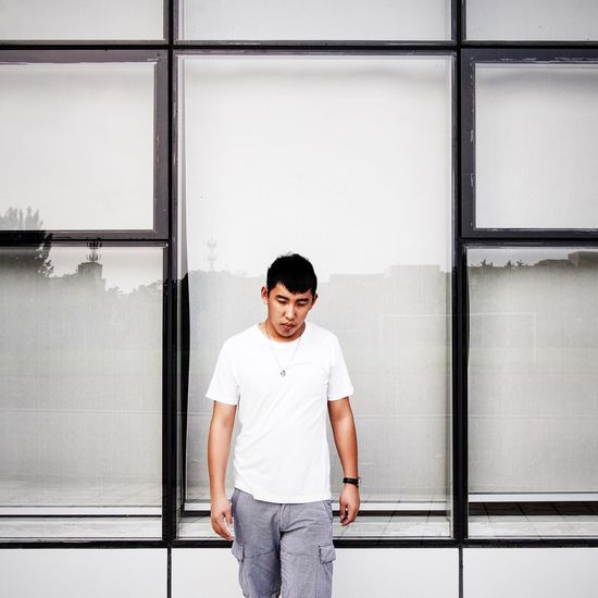 Young Man Standing In Front Of Building