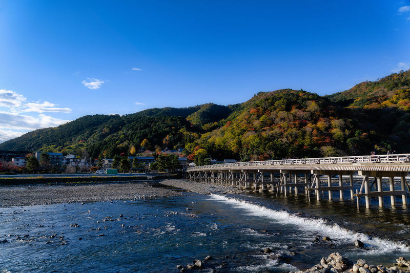 Water Sky Mountain Nature Scenics - Nature Beauty In Nature Day Architecture Tree Plant Built Structure Blue No People Tranquility Tranquil Scene Waterfront Cloud - Sky Outdoors Flowing Water Japan Kyoto Arashiyama Autumn Autumn Leaves