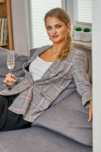 Glass Young Adult Portrait Alcohol Sitting One Person Wine Looking At Camera Young Women Indoors  Wineglass Women Drink Lifestyles Front View Refreshment Adult Leisure Activity Three Quarter Length Beautiful Woman