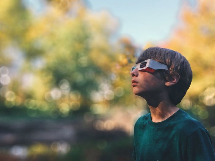 Boy wearing 3d glasses while standing outdoors