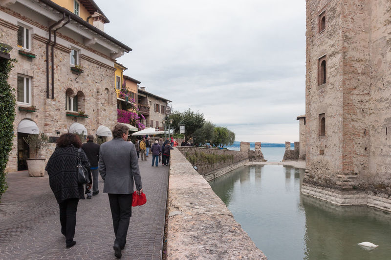 Sirmione, Italy - October 01, 2015 : Tourists walk along the embankment near the Castello Scaligero fortress wall in Sirmione, Italy Architecture Building Castello Castle Day Destination Europe Famous Fortification Fortress Garda Italy Lago Lake Lombardy Medieval Old Outdoors Scaliger Sirmione Tourism Tower Travel Wall Water