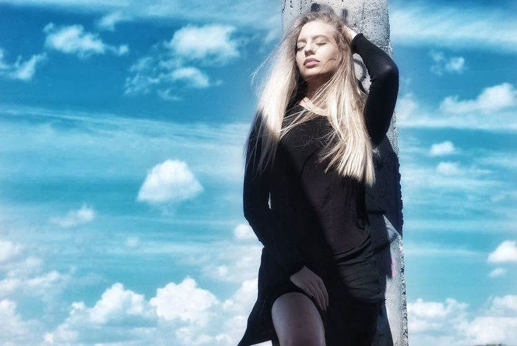 Beautiful woman posing by pole against sky