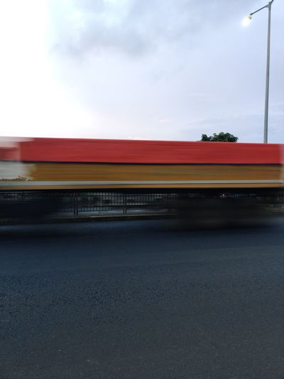 Blurred motion of train on road against sky