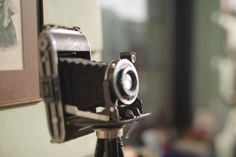 Vintage photo camera on a sunny afternoon Technology Camera - Photographic Equipment Photography Themes Focus On Foreground Close-up Photographic Equipment Camera Lens - Optical Instrument No People Retro Styled Digital Camera Antique Indoors  Nostalgia Still Life Photographing Equipment Communication SLR Camera Day