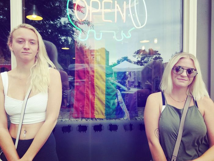 Lgbt Pride Neon Sign Day Open Sisters Young Adult Girl Women Relationship Teenager Family Blond Hair Portrait Smiling Cheerful Togetherness Multi Colored Looking At Camera Beauty Beautiful People Happiness Transparent Glass - Material Looking Through Window