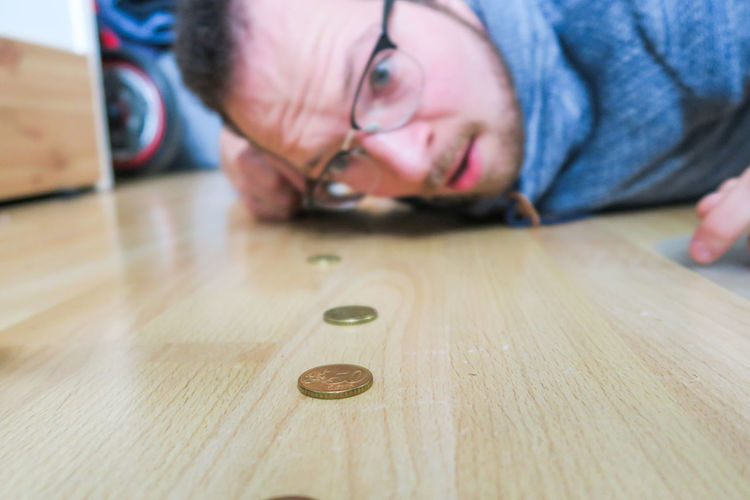 Male finding euro coins on wooden floor Wood - Material One Person Eyeglasses  Males  Coins Europe Find