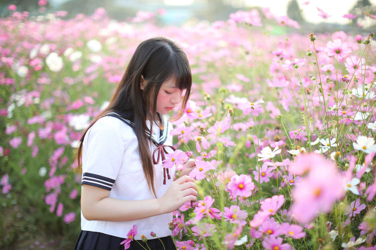 Young woman by pink flowers standing on field