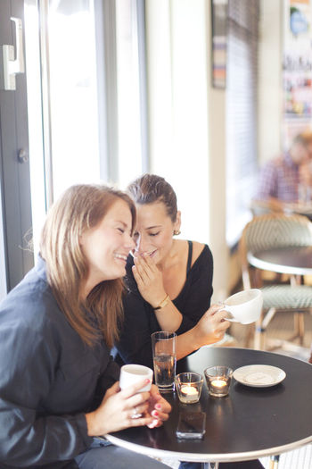 Young woman using phone while sitting at table