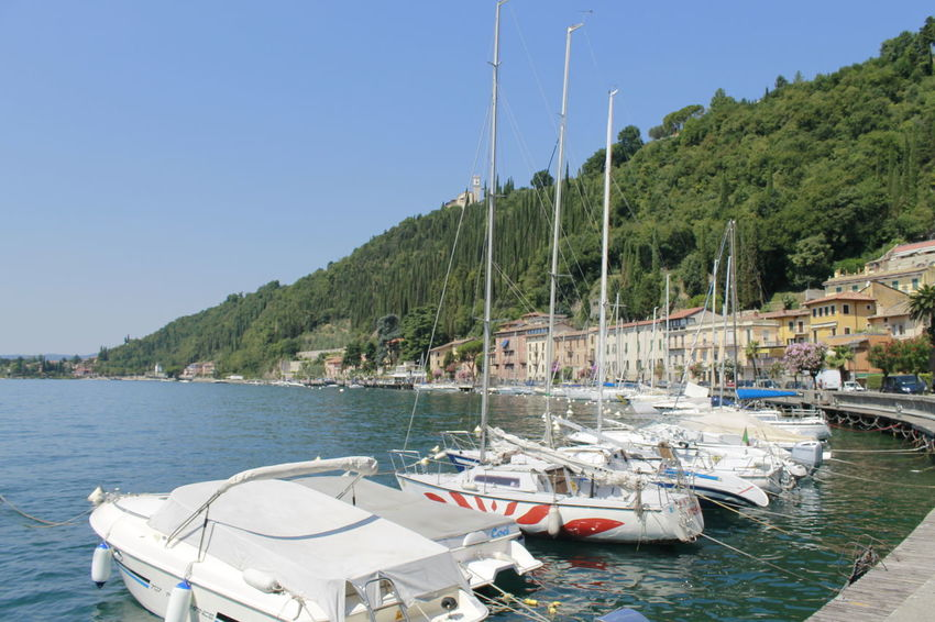 Marina in Italy Architecture Beauty In Nature Boat Clear Sky Day Garda Lake Maderno Mode Of Transport Moored Mountain Mountain Range Nature Nautical Vessel No People Outdoors Sailboat Scenics Sea Sky Tranquility Transportation Tree Water Waterfront