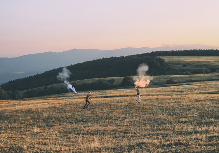 Young couple with distress flare running on field during sunset
