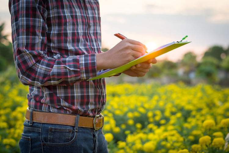 Midsection of man holding notepad while standing on agricultural field