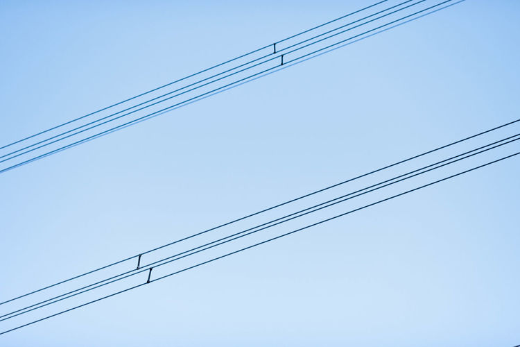 Low angle view of power cables against clear sky